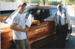 The first student, Jackson Weaver, stands with Mr. Anthony Davis, Rusty's Auto Driving School instructor, after receiving his license from Rusty's Driving School through the Third Party Test. (June, 19, 2012)